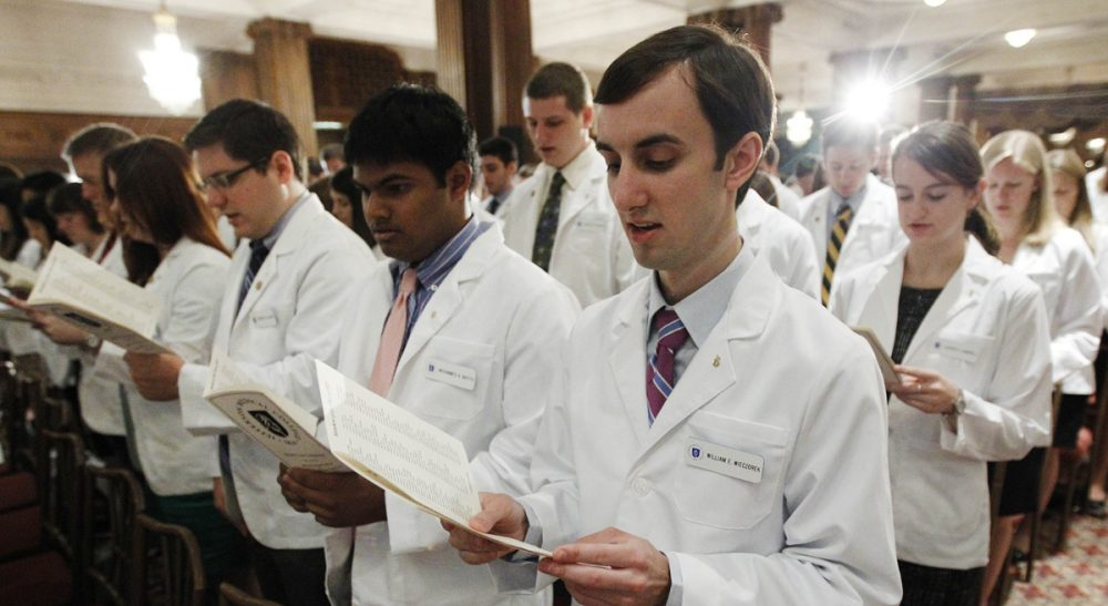 A greater understanding of healthcare economics could lead not just to lower costs -- but to better care.  In this photo, Thomas Jefferson University's Jefferson Medical College first-year student William E. Wieczorek and others take the Hippocratic Oath during the annual White Coat Ceremony, Friday, Aug. 5, 2011, in Philadelphia. (Matt Rourke/AP)
