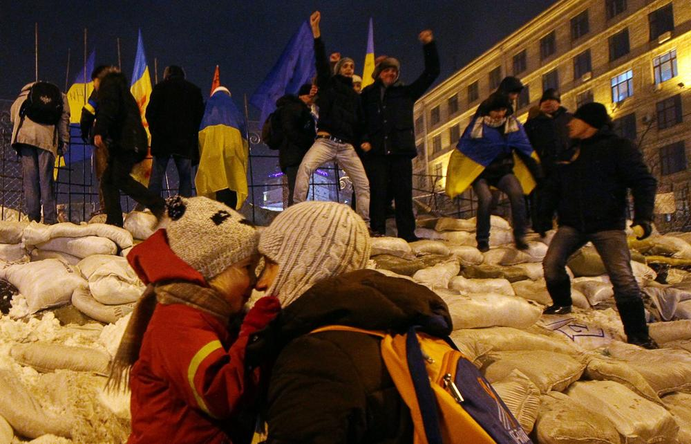 Protesters stand on their newly restored barricade in Kiev's Independence Square, late on December 11, 2013, destroyed earlier by police during a raid on the protest camp. (Sergey Gapon/AFP/Getty Images)