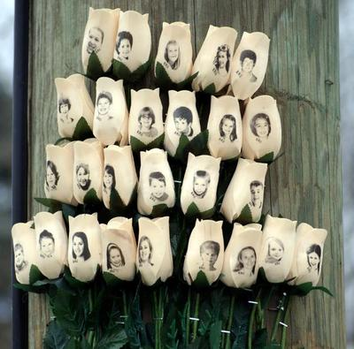 A Newtown memorial in the form of carved wooden roses, with faces imprinted, attached to a telephone pole. (Robert Carley)
