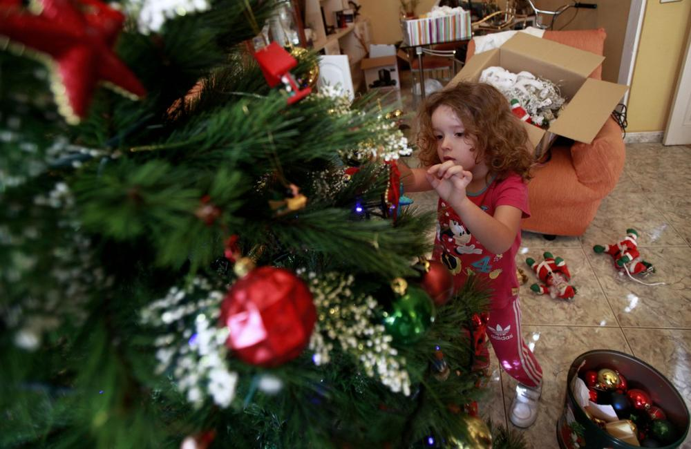 Four-year old Vera Martin prepares the Christmas tree at her home on the Spanish Canary island of Tenerife on December 8, 2013. (Desiree Martina/AFP/Getty Images)