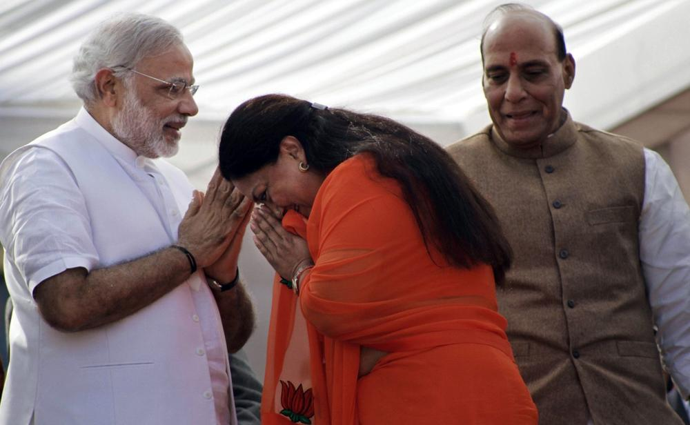 India's main opposition Bharatiya Janata Party (BJP) leader Vasundhara Raje, center, greets party prime ministerial candidate and chief minister of Gujarat state Narendra Modi, left, and party president Rajnath Singh before her oath taking ceremony as the chief minister of Rajasthan state in Jaipur, India, Friday, Dec. 13, 2013. (Deepak Sharma/AP)