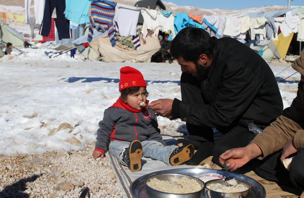 A Syrian man feeds his child in the Arsal refugee camp in the Lebanese Bekaa valley on December 15, 2013. (AFP/Getty Images)