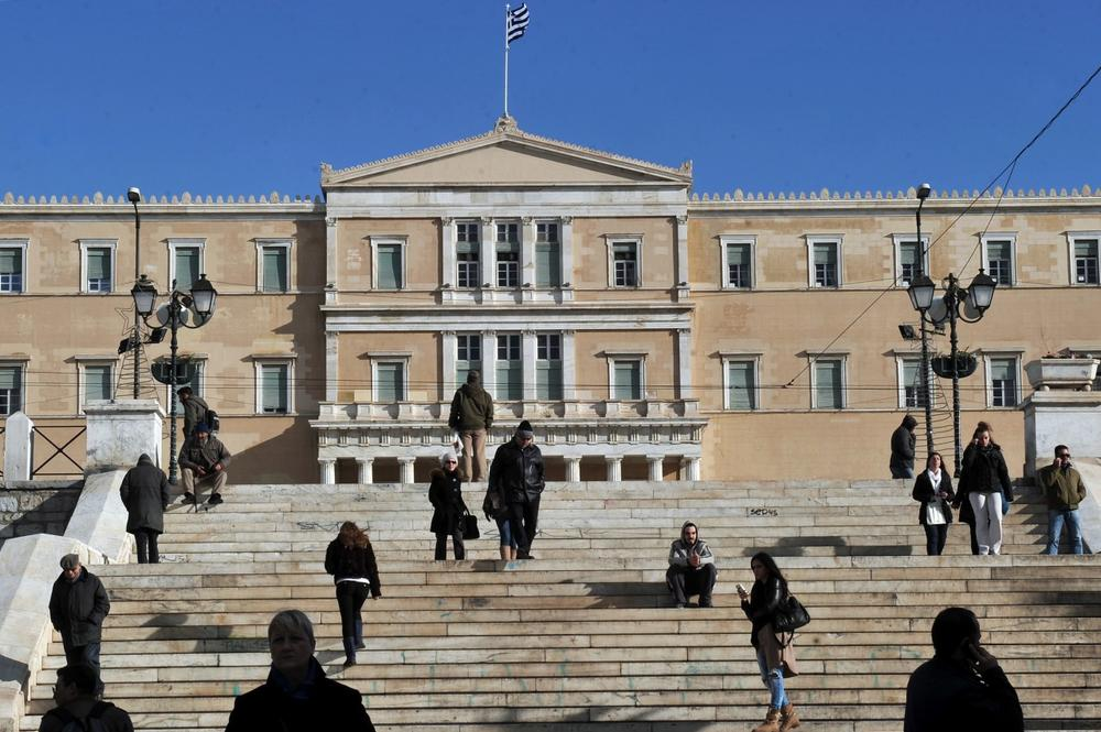 People walk in front of the Greek parliament in Athens on December 11, 2013. Greece is facing a sixth year of recession and unemployment reached 27.4 percent in September up from 26 percent in the same month last year. (Louisa Gouliamaki/AFP/Getty Images)