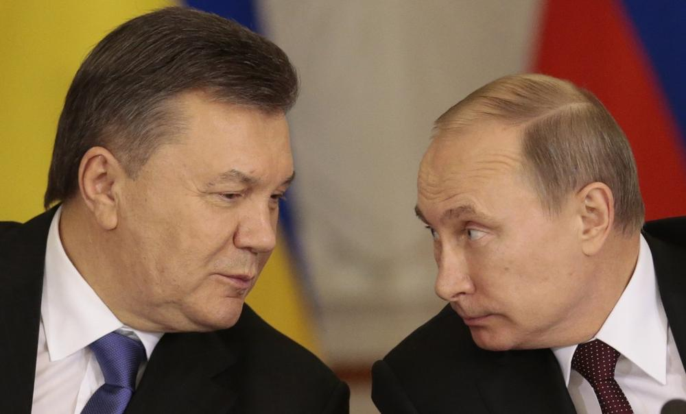 Russian President Vladimir Putin, right, and his Ukrainian counterpart Viktor Yanukovych chat during a news conference after their talks in Moscow on Tuesday, Dec. 17, 2013. (Ivan Sekretarev/AP)
