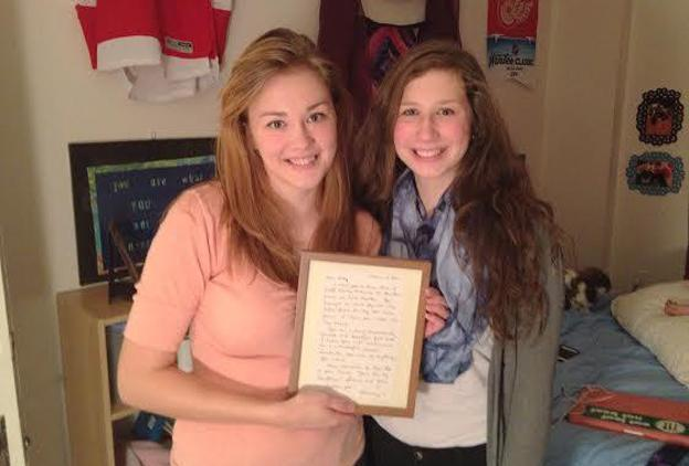 Kelly Rothe and her younger sister, Samantha. They're holding a letter written for Kelly by their mother before she died. (Kate Wells/Michigan Radio)