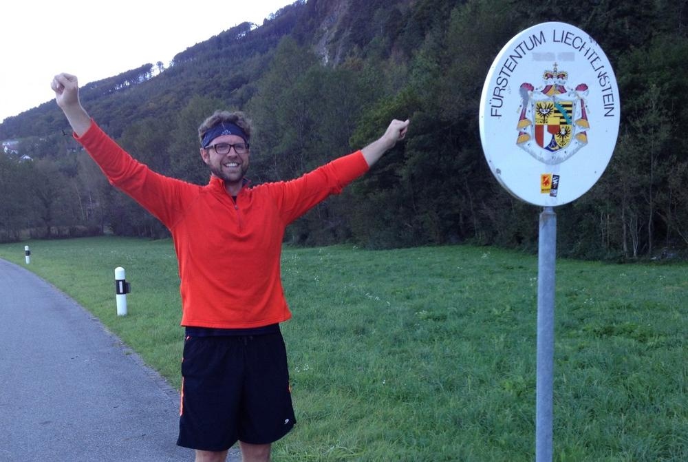Andrew Evans is triumphant at the border after running nonstop across the length of Liechtenstein (Sandra Thurnheer)