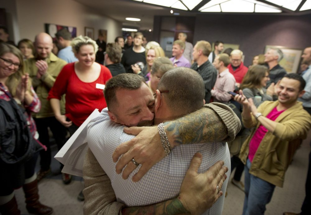 Chris Serrano, left, and Clifton Webb embrace after being married, as people wait in line to get licenses outside of the marriage division of the Salt Lake County Clerk's Office in Salt Lake City, Friday, Dec. 20, 2013. The state has requested that the court put same-sex weddings on hold while it appeals the decision.(Kim Raff/AP)