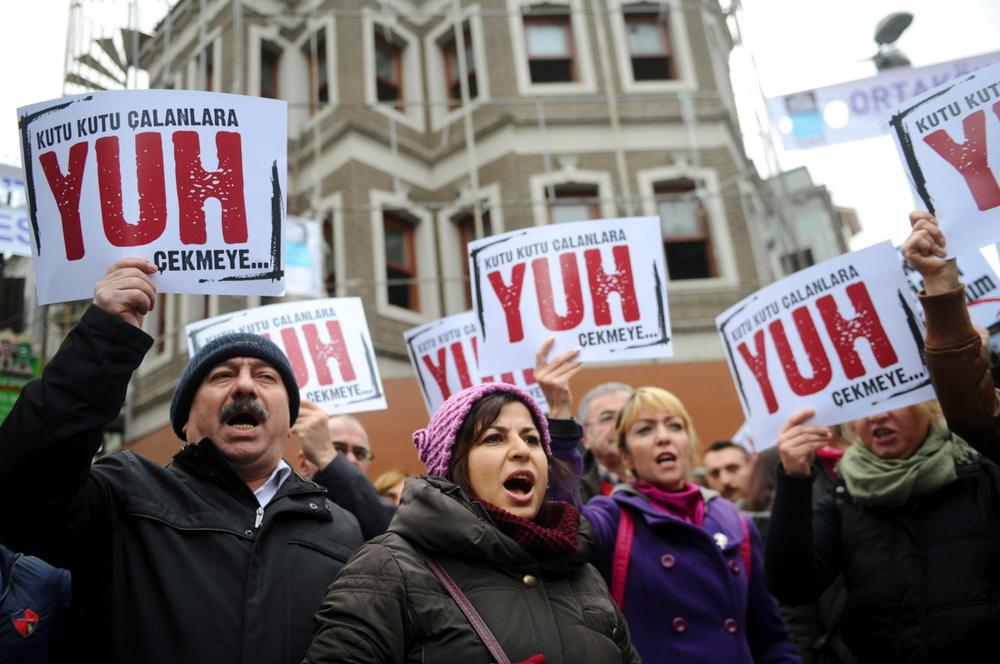 People hold placards reading 'Shame to thieves with Boxes' during a demostration on December 29, 2013 in Istanbul against corruption and the Government. Turkish Prime Minister Recep Tayyip Erdogan lashed out at the judiciary as he tried to tamp down a corruption probe that has shaken his government and sparked a new wave of anti-government protests. (Ozan Kose/AFP/Getty Images)