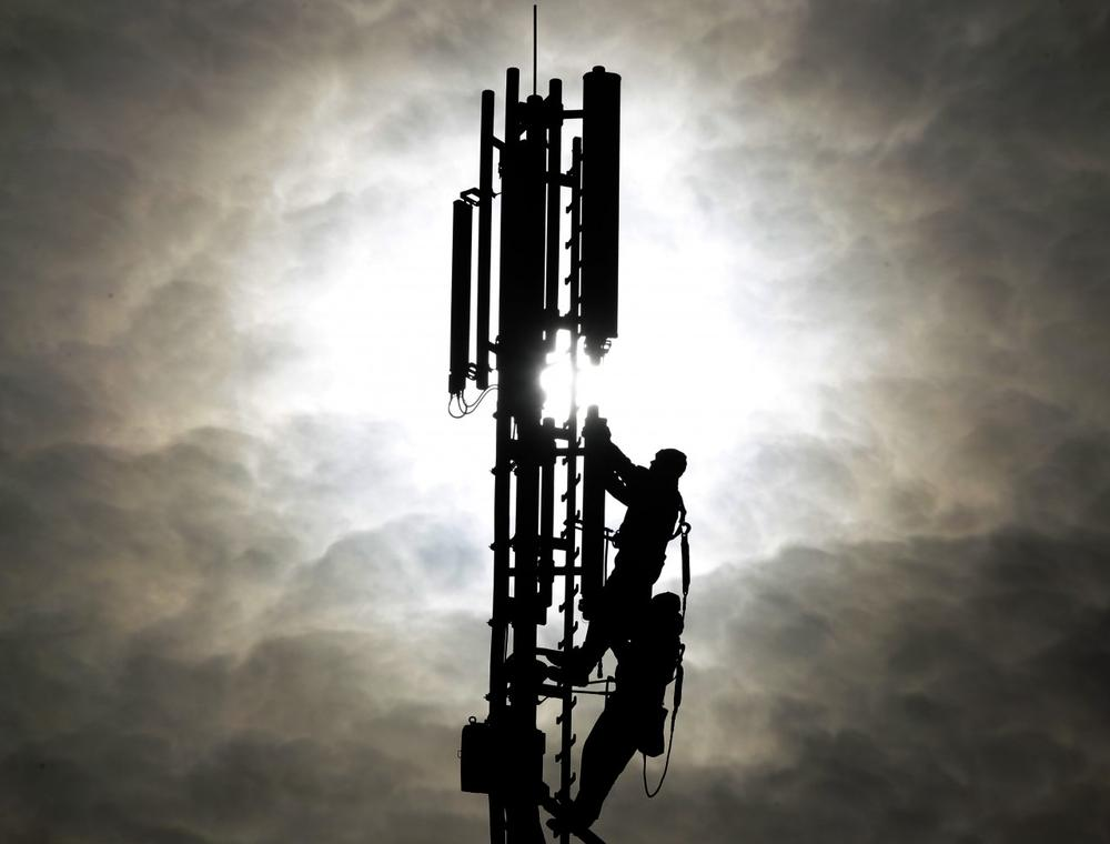 Two workers are silhouetted as they fix a mobile phone pole against the sun. (AP)