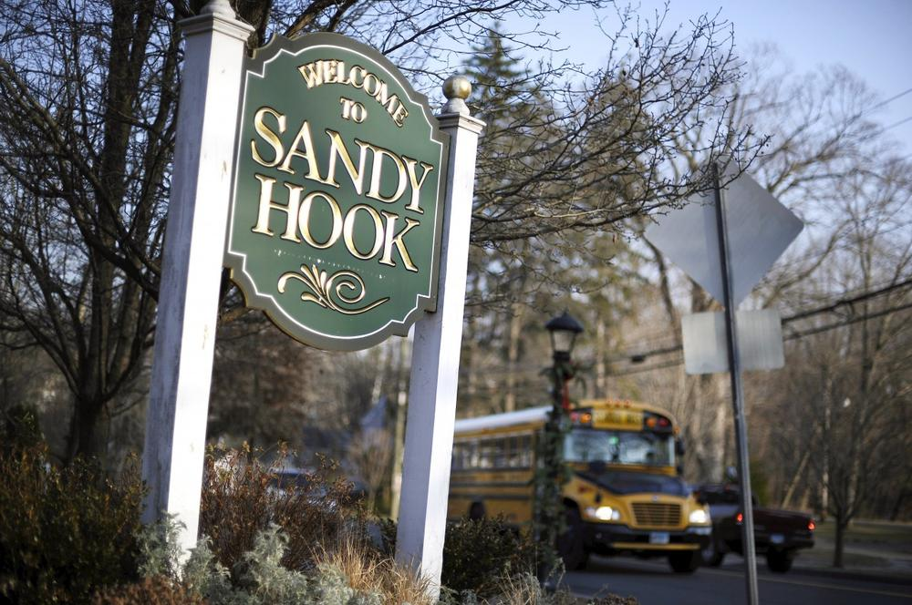 In this Dec. 4, 2013 file photo, a school bus drives past a lamppost decorated for the holidays, and a sign reading Welcome to Sandy Hook, in Newtown, Conn. (Jessica Hill/AP)