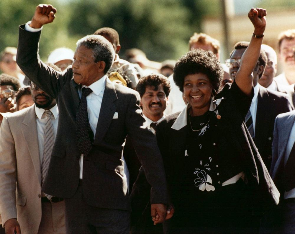In this Feb. 11, 1990 file photo, Nelson Mandela, left, and his wife, Winnie, walk out of the Victor Verster prison in Paarl, near Cape Town, South Africa, after Mandela had spent 27 years in jail. (Greg English/AP)