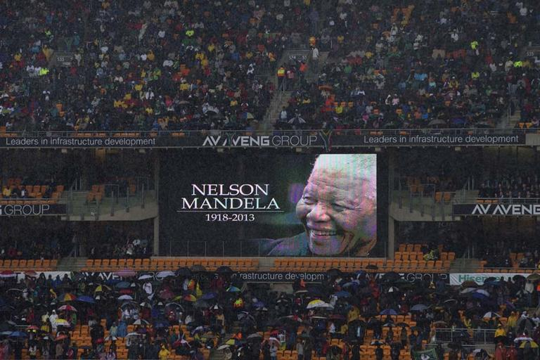 Spectators shelter under umbrellas as the rain lashes down during the memorial service for former South African president Nelson Mandela at the FNB Stadium in Soweto, near Johannesburg, South Africa, Tuesday Dec. 10, 2013. (AP)