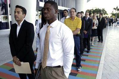 In this Wednesday, Oct. 23, 2013 file photo, Luis Mendez, 23, left, and Maurice Mike, 23, wait in line at a job fair held by the Miami Marlins, at Marlins Park in Miami. Increasingly, potential employers are turning to digital content as a way to judge job-seekers before they even apply. (AP)