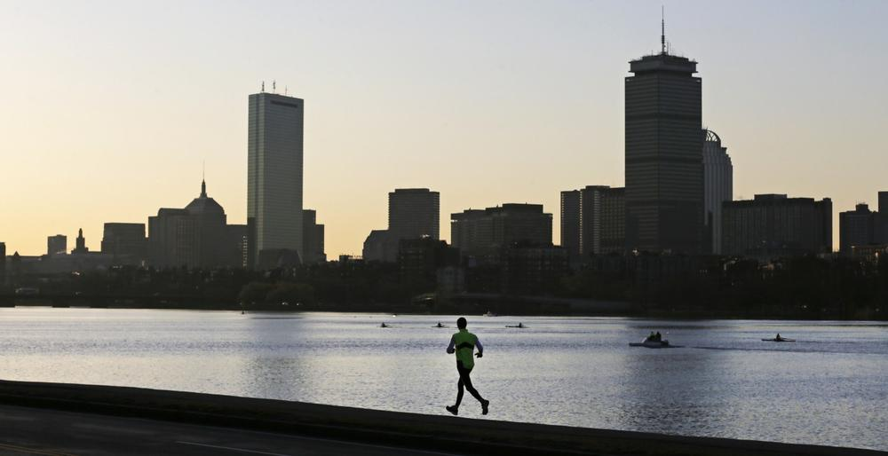 A solitary runner heads down the banks of the Charles River in Cambridge, Mass., in front of the Boston skyline, at dawn the morning after explosions killed three and injured more than 140 at the Boston Marathon, Tuesday, April 16, 2013. (AP/Charles Krupa)