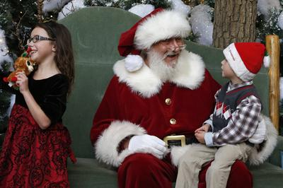 Santa chats with Asher Powell, age 6, while Asher's sister Alexis smiles during a visit to Santa's Wonderland House inside Flatirons Crossing Mall, in Broomfield, Colo., Wednesday, Dec. 18, 2013. (AP)
