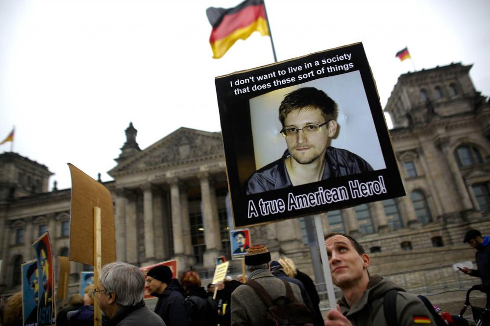Protesters hold posters of former National Security Agency member Edward Snowden in front of the German parliament building, the Reichstag, prior to a special meeting of the parliament on US-German relationships, in Berlin, Monday, Nov. 18, 2013. (AP)