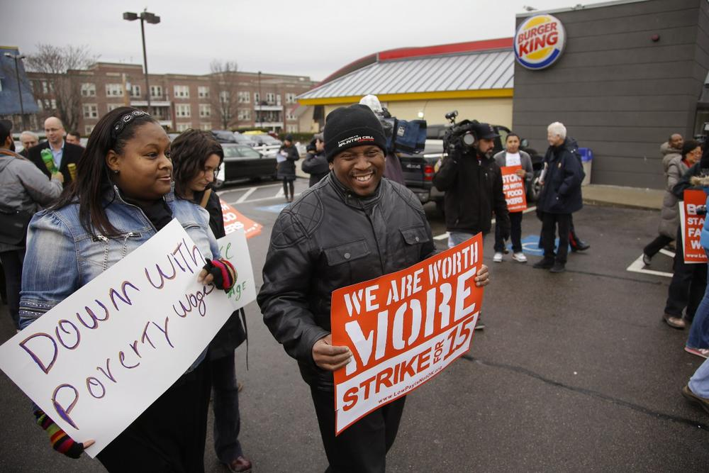 Kilra Hilton, left, and Kyle King talk while they march participating in a demonstration on a Burger King parking lot as part of a nation-wide protest supporting higher wages for workers in the fast-food industry and other minimum wage jobs in Boston, Thursday, Dec. 5, 2013. (Credit: AP/Stephan Savoia)