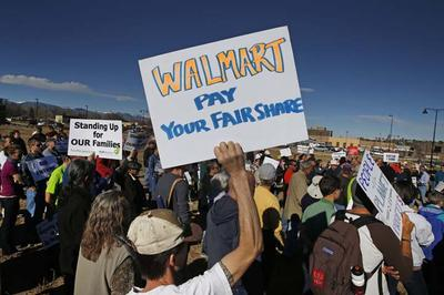 Colorado Walmart employees and supporters join nationwide protests, in front of a Walmart store in Lakewood, Colo., Friday, Nov. 29, 2013, for Walmart to publicly commit to improving labor standards. Black Friday, the day after Thanksgiving, is the nation's biggest shopping day of the year. (AP)