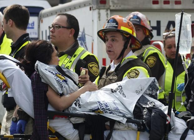 Emergency responders comfort a woman on a stretcher who was injured in one of the blasts near the Boston Marathon finish line. (Jeremy Pavia/AP)