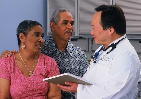 A Hispanic couple consult with an Asian doctor (National Cancer Institute via Wikimedia Commons)