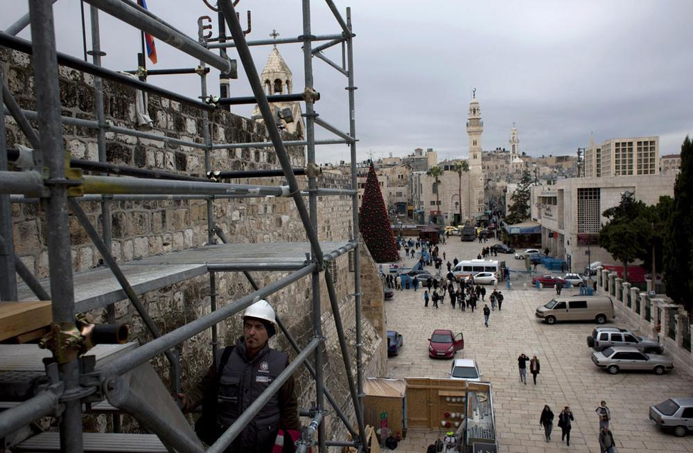 Tourists walk around the Church of the Nativity in the West Bank city of Bethlehem on Dec. 10, 2013. Wrapped in scaffolding, the basilica is having a much-needed facelift after 600 years. Last year it was included in UNESCO's list of endangered World Heritage sites. (AP Photo/Nasser Nasser)