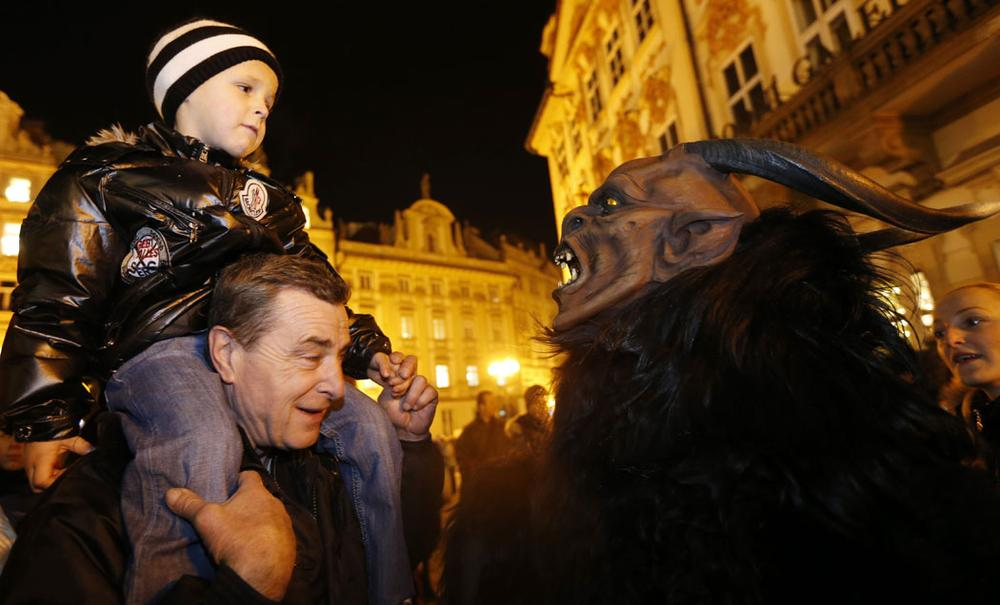 A man dressed as a devil scares a boy during a St. Nicholas parade at the Old Town Square in Prague, Czech Republic, on Dec. 5, 2012. During this traditional procession people dressed as St. Nicholas, angels and devils reward well-behaved children with small presents. (AP Photo/Petr David Josek)