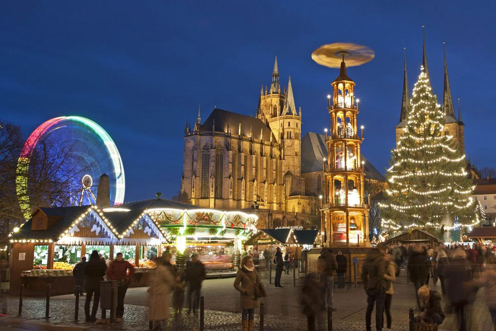 People walk along the Christmas Fair in front of the Mariendom (Cathedral of Mary) and St. Severi's Church in Erfurt, Germany, on Nov. 27, 2013. The Erfurt Christmas Market decorates the town's square with a huge candle-lit Christmas tree and a large hand-carved wooden creche. (AP Photo/Jens Meyer)