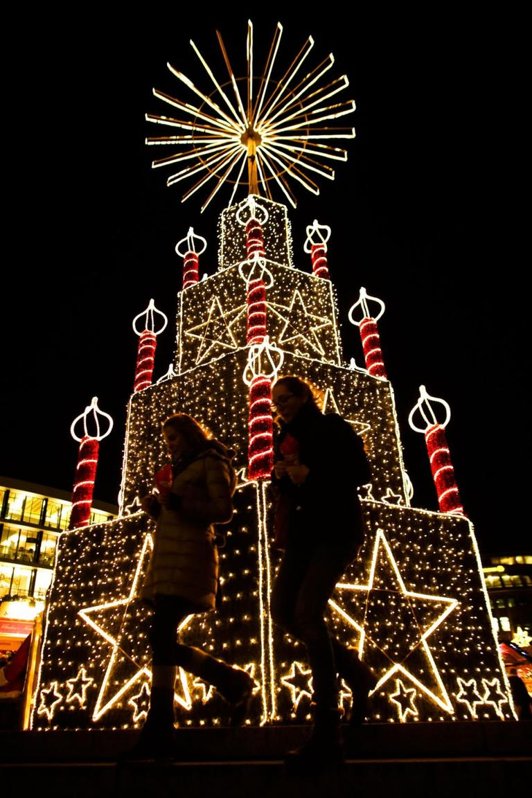 Two women walk in front of a Christmas illumination at the Christmas market at Breitscheid Place in Berlin, Germany, on Nov. 25, 2013. The opening of the markets in Berlin signifies the start of the 2013 Christmas season. (AP Photo/Markus Schreiber)