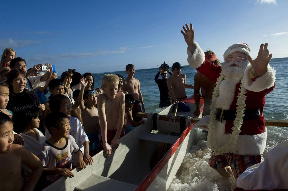 Santa Claus arrives by outrigger canoe at Waikiki in Honolulu, Hawaii, on Dec. 24, 2007. (AP Photo/Lucy Pemoni)