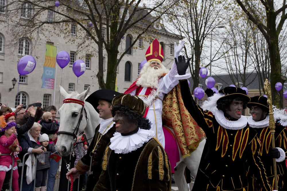 "People line a road to watch the arrival of Sinterklaas, the Dutch version of Santa Claus, and his blackface sidekicks ""Zwarte Piet,"" or ""Black Pete,"" in Amsterdam, Netherlands, on Nov. 17, 2013. Critics charge that Black Petes are an offensive caricature of black people while proponents say Pete is a figure of fun whose appearance is harmless, his face soot-stained from going down chimneys to deliver presents for the children. (AP Photo/Peter Dejong)"