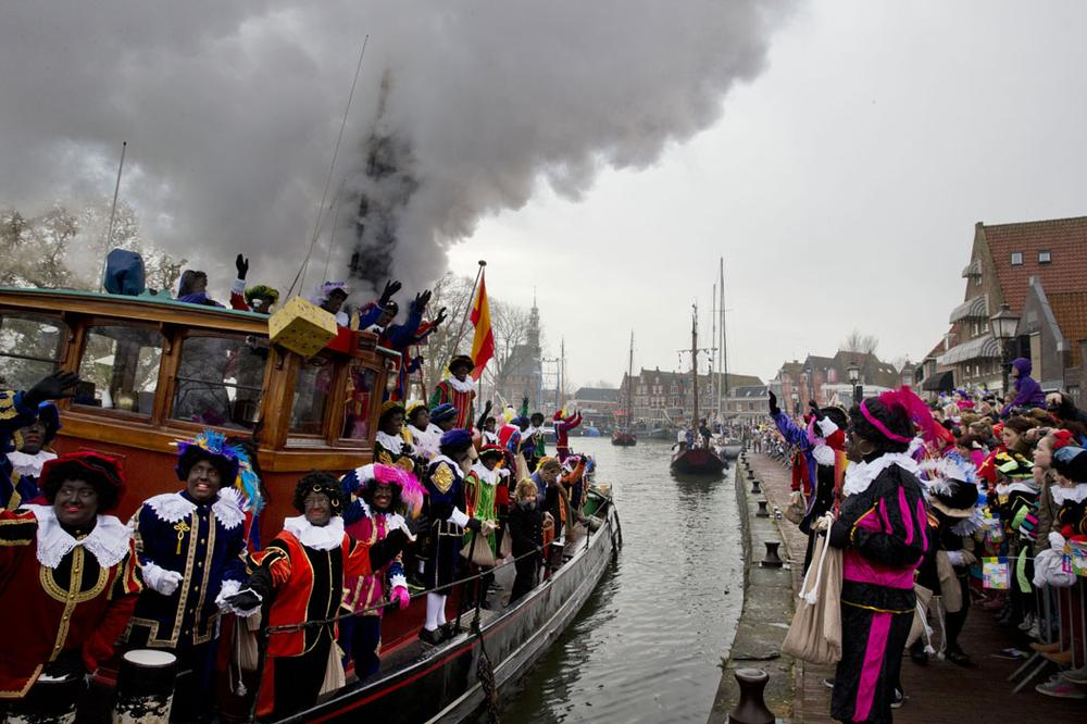 "People dressed as ""Zwarte Piet"" or ""Black Pete,"" wave to spectators as they arrive by steamboat in Hoorn, Netherlands, on Nov. 16, 2013. (AP Photo/Peter Dejong)"