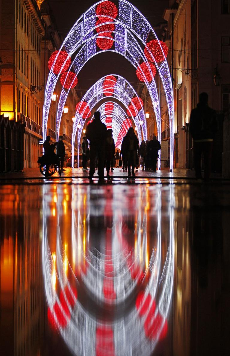 Christmas illuminations reflect on the ground in downtown Lisbon, Portugal, on Dec. 13, 2013. (AP Photo/Francisco Seco)