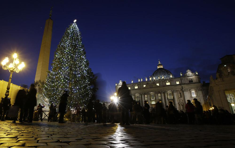 An 82-foot-tall Christmas tree from Bavaria, Germany, lights up St. Peter's Square, next to St. Peter's Basilica, at the Vatican, on Dec. 13, 2013. (AP Photo/Andrew Medichini)