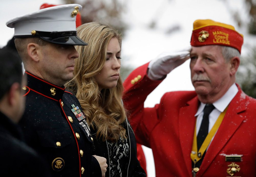 Erin Vasselian, wife of fallen Marine Sgt. Daniel Vasselian, watches as a Marine Honor Guard removes her husband's casket from a hearse at St. Bridget Catholic Church in Abington Thursday, Jan. 2. The 27-year-old was killed in combat in Afghanistan on Dec, 23, 2013. (Stephan Savoia/AP)
