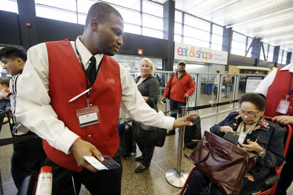 In this Tuesday, Oct. 22, 2013 photo, wheelchair attendant Erick Conley, left, assists an elderly passenger heading overseas at Seattle-Tacoma International Airport in SeaTac, Wash. (Elaine/Thompson/AP)