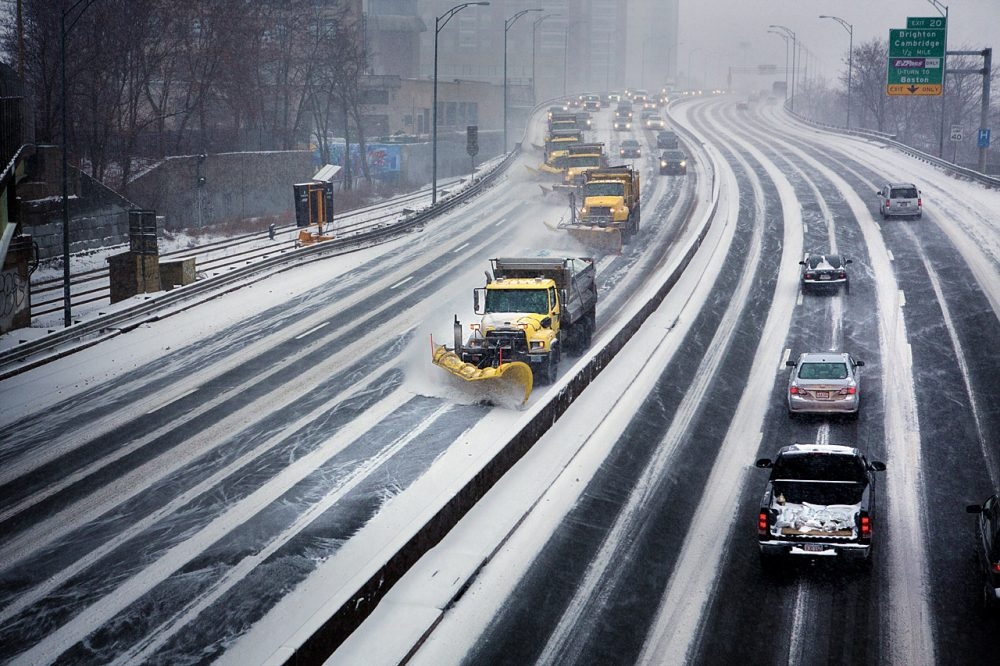 A row of snow plows moves down I-90 in Boston. (Jesse Costa/WBUR)