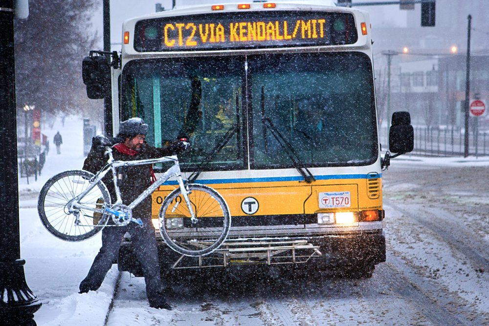 A commuter puts his bike on the front of an MBTA bus. (Jesse Costa/WBUR)