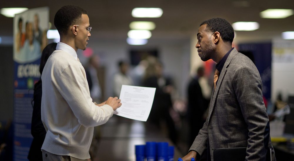 Retired U.S. Air Force Master Sgt. Thomas Gipson, of Atlanta, right, has his resume looked over by Ralph Brown, a management and program analyst with the Centers for Disease Control and Prevention, during a job fair, Thursday, Nov. 14, 2013, in Marietta, Ga. (David Goldman/ AP)