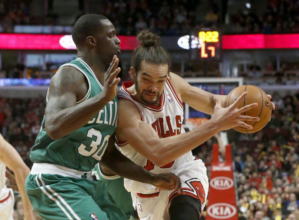Chicago Bulls center Joakim Noah, right, drives against Boston Celtics forward Brandon Bass, (Charles Rex Arbogast/AP)