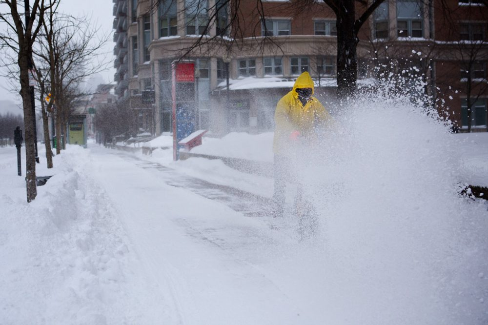 A man uses a snowplow on a sidewalk along Comm Ave in Boston Friday morning.