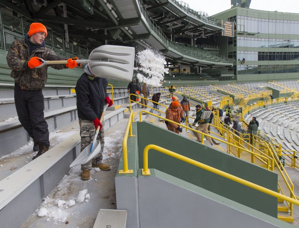 Workers clear ice and snow from the seats at Lambeau Field ahead of this Sunday's game. But, will anyone be willing to sit in them, as the forecast calls for one of the coldest games in history? (Mike Roemer/AP)