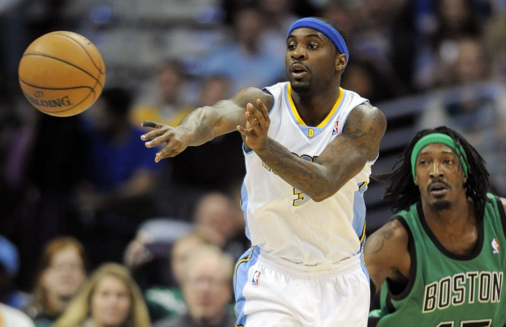 Denver Nuggets guard Ty Lawson passes the ball while being defended by Boston Celtics forward Gerald Wallace. (AP/Chris Schneider)