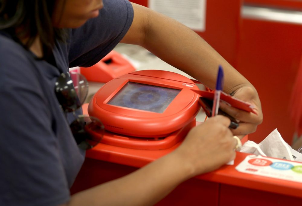 A customer signs a credit card statement next to a scanner in a Target store in Miami, Florida. The malicious computer tool used against the retailer in its massive credit card breach, called Kaptoxa, was revealed in a government report released January 16.  (Joe Raedle/Getty Images)