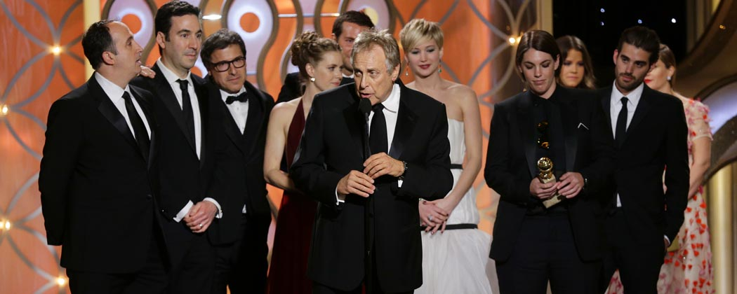 """Charles Roven, center, accepts the award for best motion picture comedy for """"American Hustle."""" (Paul Drinkwater/NBC/AP)"""