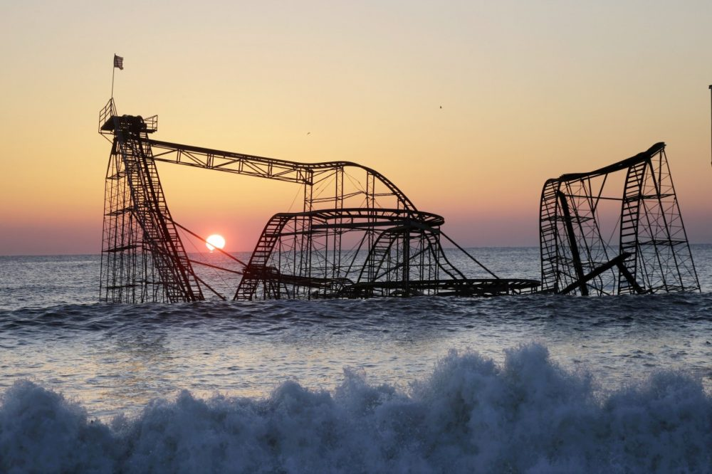 The sun rises in Seaside Heights, N.J. behind the Jet Star Roller Coaster which has been sitting in the ocean after part of the Funtown Pier was destroyed during Superstorm Sandy. (Mel Evans/AP)