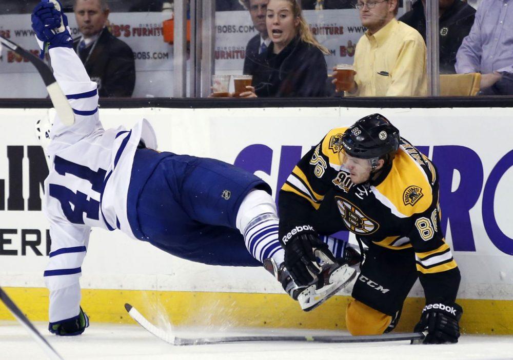 Boston Bruins defenseman Kevan Miller (86) takes down Toronto Maple Leafs left wing Nikolai Kulemin (41) in the third period. (AP/Elise Amendola)