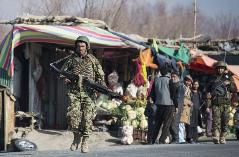 An Afghan National Army (ANA) soldier passes shops during an exercise in Poll-e-Matack, north of Kabul, on January 14, 2014.  (Johannes Eisele/AFP/Getty Images)