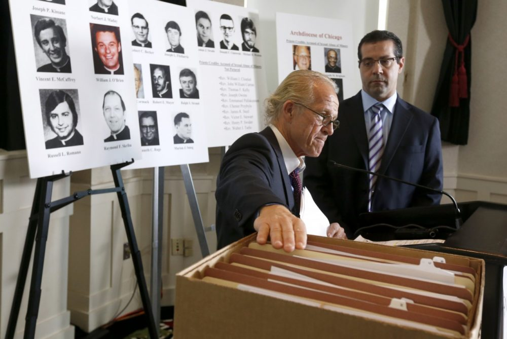 Attorney Jeff Anderson, left, places his hand on the files of Catholic priests credibly accused of sexually abusing minors in the Archdiocese of Chicago, prior to a news conference Tuesday, Jan. 21, 2014, in Chicago. Joining Anderson is attorney Marc Pearlman. (Charles Rex Arbogast/AP)
