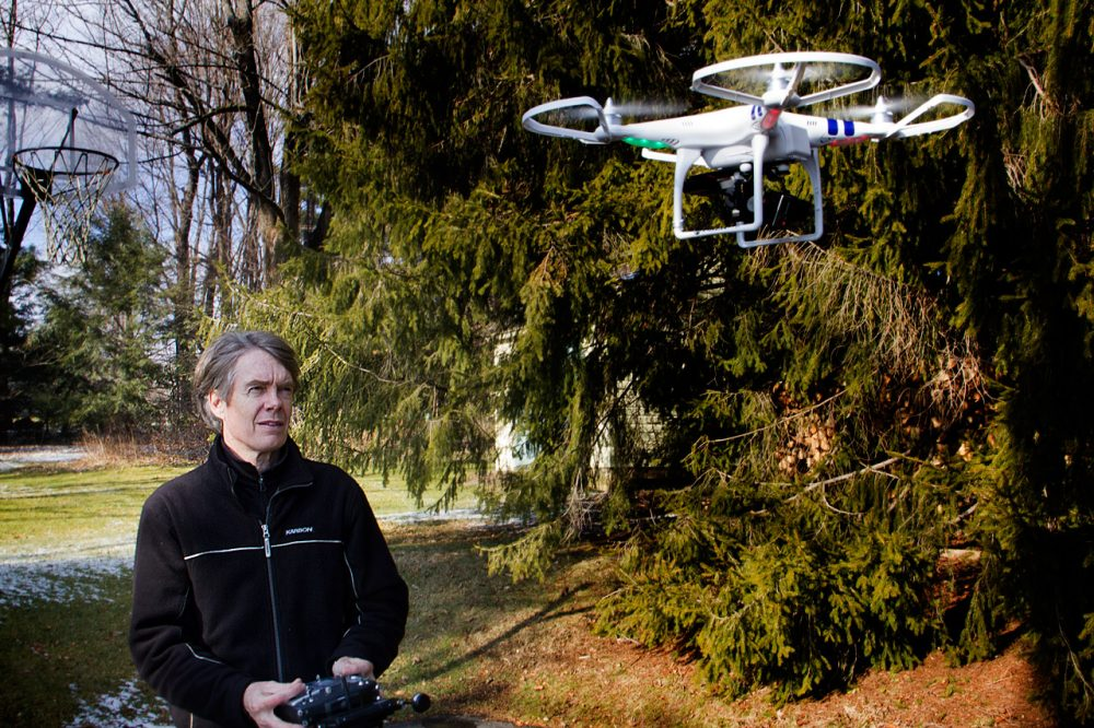 "Entrepreneur Terry Holland operates his ""quadcopter"" unmanned aerial vehicle outside his Pittsfield home. (Jesse Costa/WBUR)"