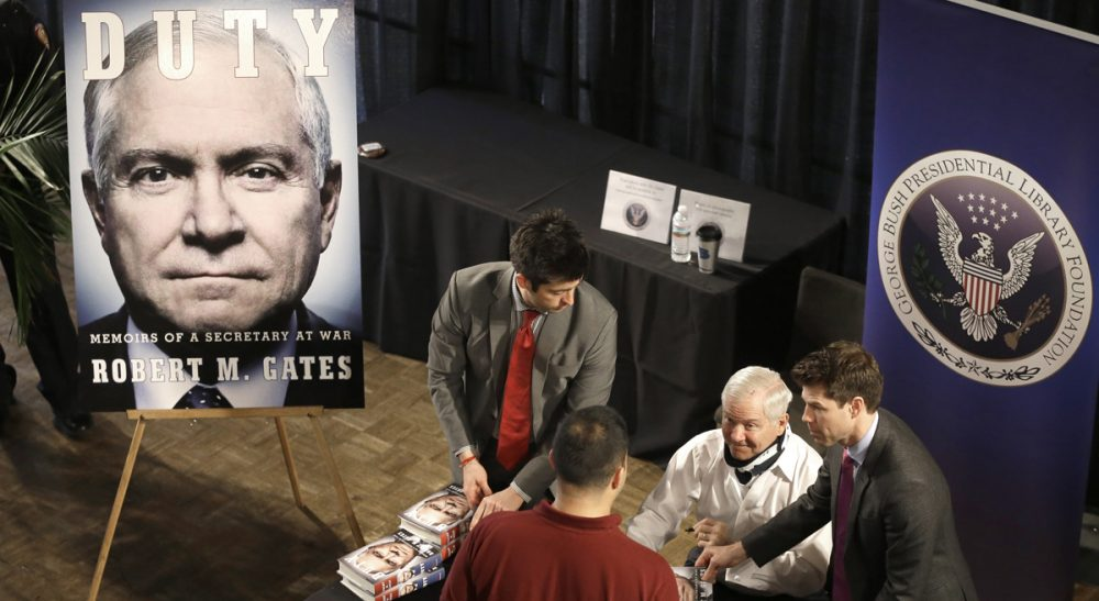 Over the course of four decades, former defense secretary Robert Gates had an enormous impact on U.S. national security. Based on a close reading of his new memoir, John Sivolella says it appears he might not be finished.  In this photo, wearing a neck brace after a fall a few weeks ago, Gates, second from left, signs copies of his new book after speaking at Texas A&M University Tuesday, Jan. 21, 2014, in College Station, Texas. (Pat Sullivan/AP)